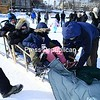 Sled dog handler Colin Campbell (right) prepares a blanket to cover visitors taking a dog sled ride around Mirror Lake in Lake Placid, where temperatures dipped to 10 below zero Sunday. Sled dog team owner John Houghton said that so far the season has been good with plenty of tourists in the Olympic Village and about 10 inches of ice on the lake. He said that in some previous years Mirror Lake did not freeze over enough for the holidays to allow rides on the lake.<br /> JACK LADUKE/ P-R PHOTO