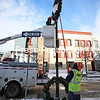 Plattsburgh Municipal Lighting Department worker Jim Baker (right) positions a pole to help Garrett Mastic as he removes a holiday wreath from a streetlight on Margaret Street. The wreaths bring holiday spirit to downtown yearly during their brief time on display.<br /> KAYLA BREEN/ STAFF PHOTO