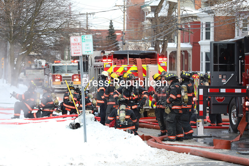 Plattsburgh City Fire Department crews put on self-contained breathing apparatuses before heading back inside the burning.<br /> KAYLA BREEN/ STAFF PHOTOS