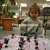 Two-year-old Enziatta Allen escapes the cold with her mom and entertains herself with a miniature hockey table at the Plattsburgh Public Library. With the cold continuing, more parents will be looking for indoor kid activities this week.<br /> KAYLA BREEN/ STAFF PHOTO