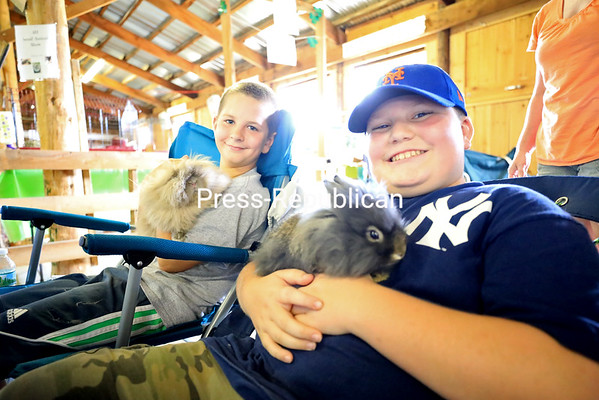 Eleven-year-old Josh Daniels (left) and his best friend, Collin LaDuke, 11, hold lionhead rabbits Peanut and Chip inside the 4-H Barn during the 70th-annual Clinton County Fair in Plattsburgh. The boys belong to Clinton County Cornell Cooperative Extension 4-H Youth Club the Rabbit Den, based in Keeseville. The Rabbit Den members learn skills that deal with the animal science of rabbits and other small rodents like cavies. The cavy family, native to South America, includes the domestic guinea pig, wild cavies and the capybara. KAYLA BREEN/ Staff Photo