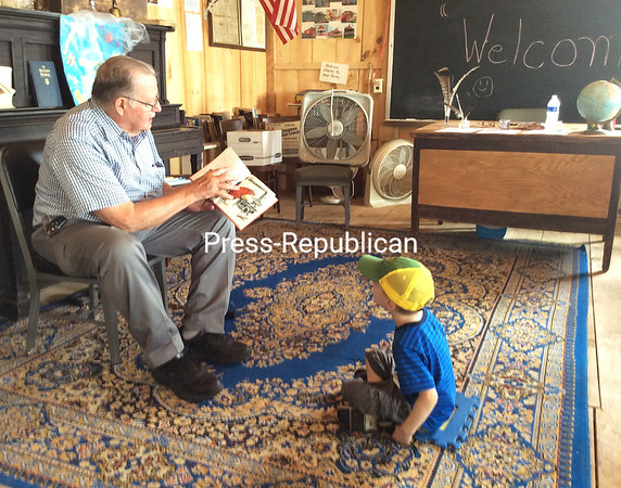 Bob Cheeseman reads a children's book to Carter Bierman, who was with his grandfather Brain Lavarnway at the Clinton County Fair. ROBIN CAUDELL/ Staff photos