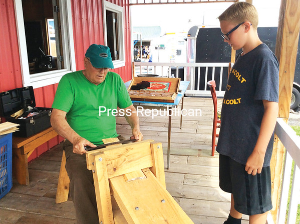 Larry Bosley teaches Payton Blazima how to make a shingle on a shaving-horse demonstration at the Little Red Schoolhouse at the Clinton County Fair. ROBIN CAUDELL/ Staff photos