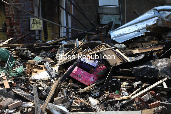 A bright pink and purple Beetle convertible toy sits partially buried among the charred rubble of the apartment house destroyed by flames Sunday. Two attached buildings were saved by the efforts of some 150 firefighters from numerous departments. KAYLA BREEN/ Staff photo