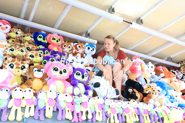 Carnival worker Shannon Kirkpatrick sets up stuffed animals along the rafters of a game booth as she prepares for the opening of the Clinton County Fair. The fair will be held through Sunday and will feature country music artist Ronnie Milsap, along with other family friendly entertainment like freestyle motocross and Michael Blaine's hypnotist performance. For a full schedule of events, check out the Press-Republican's 2018 Clinton County Fair Guide at pressrepublican.com. KAYLA BREEN/ Staff photo