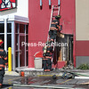 Plattsburgh City Fire Department firefighters use a chainsaw to cut a hole in an outer wall of Kentucky Fried Chicken at 333 Cornelia St. as they work to douse hot spots after a fire at the restaurant Tuesday. An early determination indicated a tossed cigarette had sparked the blaze.<br /> KAYLA BREEN/ Staff Photo