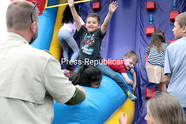 Rich Hoogkamp, the assistant scout master of Beekmantown Boy Scout Troop 8046, manipulates the center divider of an inflatable slide to the joy of Willona Sataeeskumar, 6, of Plattsburgh, to create an even more enjoyable ride during the annual St. Peter's Church Festival in Plattsburgh. The scouts volunteered their time to help setup and coordinate booth games throughout the day. The event, which serves as a fundraiser for ministries of the church, featured children's games, food, live music, a book sale, flea market, raffles and more.<br /> GABE DICKENS/ P-R photo