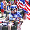 """Ryan Cogswell, as """"Freedom Franky,"""" drives his motorized and very patriotic sofa chair past the Macdonough Monument and waves at the crowd as he participates in Fourth of July parade in the City of Plattsburgh.<br /> KAYLA BREEN/ STAFF PHOTO"""