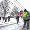Crossing Guard Maurice Daniels doesn't let falling snow and cold temperatures bother him as he stops traffic to let students from Stafford Middle School walk the slick crossing lane at the intersection of Broad and Oak streets in Plattsburgh on Friday afternoon. The storm that buried other areas of the state was kinder to the North Country, though several vehicles slid off snowy roads over the course of the day.<br /> KAYLA BREEN/ STAFF PHOTO