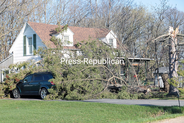 A pine tree that snapped off about 20 feet from the ground came to rest between this sport utility vehicle and the house located at 76 Moffit Road in the Town of Plattsburgh. GABE DICKENS/ P-R photo