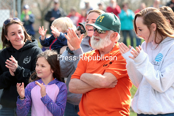 Hector Duquette stands with his family as he is honored for his 34 years of service as a Plattsburgh Little League coach Saturday with a commemoration ceremony and a plaque unveiling, officially naming the baseball field Hector Duquette Field, prior to the official opening day for Little League baseball at Melissa L. Penfield Park in Plattsburgh. GABE DICKENS/ P-R PHOTOs