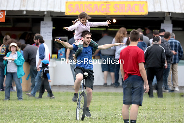 Olivia Walker, 7, of Plattsburgh, rides on the shoulders of performer Schuyler Gratto of Morrisonville as he pilots his unicycle in circles at the 51st Bazaar and Memorial Day Celebration in Champlain. GABE DICKENS/ P-R photo