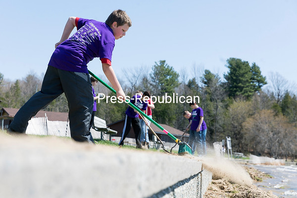 Gavin Barber, 12, of Beekmantown, sweeps sand and dirt off the sidewalk adjacent to the Point au Roche State Park beach during the recent New York State I Love My Park Day, hosted by the Friends of Point au Roche State Park. Barber, a member of Boy Scout Troop 8046 in Beekmantown, joined nine fellow scouts in sprucing up the park and planting 21 trees and shrubs. The troop was part of a much larger contingent of volunteers who pitched in on various tasks, including picking up garbage and gardening near the visitors center. GABE DICKENS/ P-R PHOTO