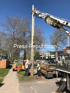 On Wednesday, City of Plattsburgh Municipal Lighting Department employees Jordan Hicks (left), Billy Brown and, controlling the digger (not seen), Dave Bazio, set a new power pole in place on the west side of Cornelia Street opposite LaFayette Street that will take the load as poles across the street are replaced due to damage from Friday's windstorm. A 60-foot pine that blew down on LaFayette Street landed on power lines and caused a utility pole near the Cornelia Street intersection — some distance away — to snap. That one and the one next to it, which was badly cracked, were slated for replacement. SUZANNE MOORE/ STAFF PHOTO