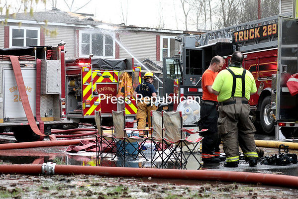 Firefighters take a break while others continue applying water to the exterior of an apartment building at 40 Adirondack Lane to ensure any hot-spots are extinguished following a blaze that destroyed a portion of the structure Sunday afternoon in Plattsburgh. GABE DICKENS/ P-R photo