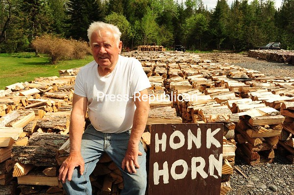 George La Flamme, 83, of Tupper Lake, sits on of 100 cords of camp wood he sells to summer campers. But rising gas prices have La Flamme worried that the number of tourists traveling this summer will drop, reducing his sales. La Flamme sells dried birch wood by the bundle for $30.00 He has been selling camp wood for more than 50 years. JACK LADUKE/ P-R photo