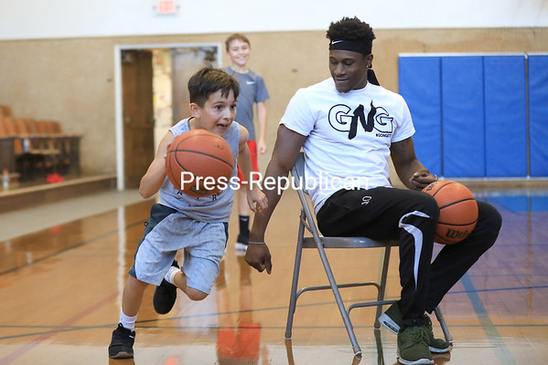 Eleven-year-old Carson Haywood (left) dodges trainer Tre Bucci as he makes his way toward the basket during a driving chair drill as his friend Gavin LaVarnway, 10, watches and waits for his turn during a recent GNG Fitness basketball skills class at the AuSable Forks Community Center gym. The class, which is every Monday, Wednesday, Friday and occasionally weekends, focused on techniques like ball handling, free throws and some one-on-one games. Haywood and LaVarnway have been taking basketball skills and speed and agility classes from Bucci for more than six months now.<br /> KAYLA BREEN/ Staff photo