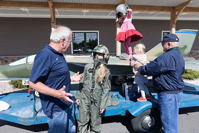 Peru resident Bridget Molloy chats with Joe McNichols, a retired U.S. Air Force colonel, while trying on a flight suit and one of his pilot helmets; the other being worn haphazardly by her daughter, Ella, 5, while her youngest, Winnie, 3, is helped onto a replica of a FB-111A Aardvark by Vietnam Veteran Frank McGrath during Veterans and Military Appreciation Day co-hosted by the North Country Veterans Association and Lenny's Shoe and Apparel in Plattsburgh recently. The event served as a fundraiser for a building expansion at the North Country Veterans Association Center located at 27 Townline Road in Plattsburgh and featured informational booths staffed by local military and veterans organizations that offer support programs for veterans and their families. The jet, which was recently acquired by McNichols, features a lawn mower engine and smoke generator to mimic a jet's contrails left in the sky. McNichols plans to feature the jet, whose full-size counterpart he piloted, in area parades and at the Plattsburgh Air Force Base Museum. GABE DICKENS/ P-R photo