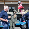 Peru resident Bridget Molloy chats with Joe McNichols, a retired U.S. Air Force colonel, while trying on a flight suit and one of his pilot helmets; the other being worn haphazardly by her daughter, Ella, 5, while her youngest, Winnie, 3, is helped onto a replica of a FB-111A Aardvark by Vietnam Veteran Frank McGrath during Veterans and Military Appreciation Day co-hosted by the North Country Veterans Association and Lenny's Shoe and Apparel in Plattsburgh recently. The event served as a fundraiser for a building expansion at the North Country Veterans Association Center located at 27 Townline Road in Plattsburgh and featured informational booths staffed by local military and veterans organizations that offer support programs for veterans and their families. The jet, which was recently acquired by McNichols, features a lawn mower engine and smoke generator to mimic a jet's contrails left in the sky. McNichols plans to feature the jet, whose full-size counterpart he piloted, in area parades and at the Plattsburgh Air Force Base Museum.<br /> GABE DICKENS/ P-R photo