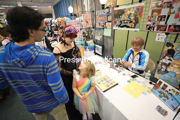 Five-year-old Mylie Ambrosio, dressed as a fairy princess, looks up at her friends Dakota Rabideau (center), dressed as a demon enchantress, and Cole Robare (left) as they purchase anime character pins, made by local artist Jennelle Chartier, from Adam McBrayer during the third-annual Plattsnerd celebration at Champlain Centre mall in Plattsburgh. The event, sponsored by PBS, featured a cosplay convention, vendor tables featuring local artists, gaming talk and selfie booths. KAYLA BREEN/ STAFF PHOTO