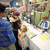Five-year-old Mylie Ambrosio, dressed as a fairy princess, looks up at her friends Dakota Rabideau (center), dressed as a demon enchantress, and Cole Robare (left) as they purchase anime character pins, made by local artist Jennelle Chartier, from Adam McBrayer during the third-annual Plattsnerd celebration at Champlain Centre mall in Plattsburgh. The event, sponsored by PBS, featured a cosplay convention, vendor tables featuring local artists, gaming talk and selfie booths.<br /> KAYLA BREEN/ STAFF PHOTO