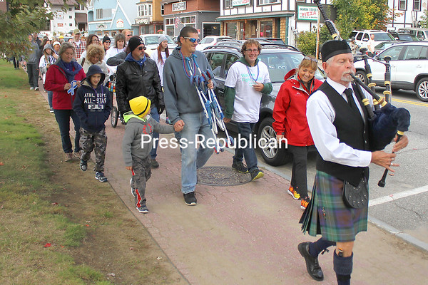 Led by bagpiper John Radigan, participants march in the 10th-annual North Country Out of the Darkness Community Walk held Sunday in Lake Placid. The fundraiser walks are organized nationwide, with funds raised in North Country walks helping fund awareness and support activities by the New York Capitol Region of the American Foundation for Suicide Prevention. That region includes Clinton, Essex and Franklin counties. The 2018 North Country walk had raised $21,623 of a $35,000 goal by Tuesday afternoon. Donations can still be made toward that goal until Dec. 31 at tinyurl.com/y9c72zxb.<br /> BEN ROWE/ STAFF PHOTO