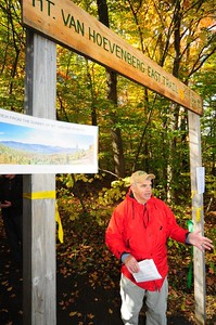 Adirondack Mountain Club Executive Director Neil Woodworth stands at the entrance to the new East Trail on Mount Van Hoevenberg in the Town of North Elba on Friday, when the newest trail in the Adirondacks was opened to the public just in time for Columbus Day weekend. Woodworth congratulated the State Department of Environmental Conservation for creating the hiking trail, while Assemblyman Dan Stec (R-Queensbury), who also attended the official opening, said that he will continue to campaign for the hiring of more badly needed DEC forest rangers. The 1.7-mile trail, which climbs 920 feet to its 2,940-foot summit, was designed and built to withstand heavier use, the DEC and Olympic Regional Development Authority said in a press release. Bench cuts send water across the path instead of down it, while heavy turnpike construction and tread hardening aim to combat erosion. And the route, DEC said, avoids extremely steep areas to make the hike less strenuous. The trailhead is at the Olympic Sports Complex at 220 Bobsled Run Road. JACK LADUKE/ P-R Photo