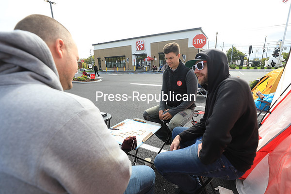 Friends Zach Stephenson (left), Keith Sampere (center) and David Perry enjoy a game of Scrabble as they kill time while participating in the Chick-fil-A First 100 Campout outside the new Plattsburgh eatery. The 24-hour long event, which started at 6 a.m. Wednesday, invites locals to stay overnight in the Chick-fil-A parking lot to earn 52 free chicken sandwich meals. Stephenson, an experienced Chick-fil-A's First 100 Campout participant, told his friends in advance to get the day off so they could join in on the fun. Stephenson and Sampere traveled from Vermont; Perry lives in Plattsburgh.<br /> KAYLA BREEN/ STAFF PHOTO