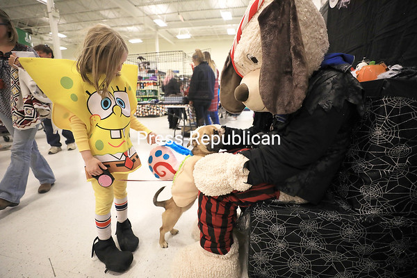 Dressed as Nickelodeon characters Spongebob Squarepants and Gary the Snail, 6-year-old Zoey Theisen and her 6-month-old beagle mix, Lulu, visit with mascot Chance the dog during the recent PetSmart Halloween Spooktacular event in Plattsburgh. Pets and their parents dressed in their Halloween best to participate in a costume parade, trick-or-treating and other holiday-themed events. KAYLA BREEN/ Staff photo