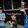 Everett Feeley lifts his second-place Zucchini Races trophy in jubilation, not minding in the least that Zakok Ives (left) captured first place. Jax Feeley (center) admires the trophy he won in the event.<br /> ALVIN REINER/ P-R photos
