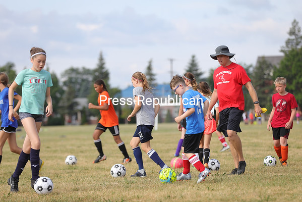 Coach Tim Mulligan watches as participants practice dribbling and other soccer skills during the Plattsburgh Soccer Camp at the U.S. Oval. The week-long camp features boys and girl ages six to 18 years old and focuses on soccer skills. Each participant receives a soccer ball and camp t-shirt.<br /> KAYLA BREEN/ STAFF PHOTO