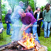 Members of the New Land Trust in Saranac share stories around the fire before enjoying a potluck dinner.<br><br>(Gabe Dickens/P-R Photo)
