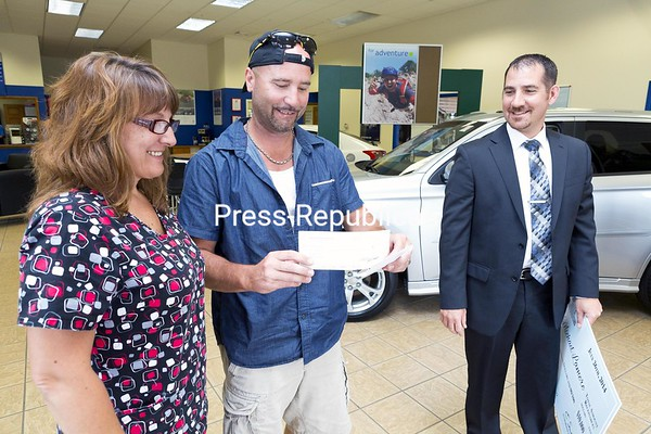 Michael Lamere and his wife, Tammy, of Keeseville admire a check for $10,000 just presented to him by Della Mitsubishi General Sales Manager Ed Savage in Plattsburgh Tuesday afternoon. Despite skepticism from Tammy, Michael brought in a mailer from the dealership that turned out to match the winning numbers posted on a prize board in the showroom. Engaged to get married, the couple tied the knot two days later.<br><br>(GABE DICKENS/P-R PHOTO)