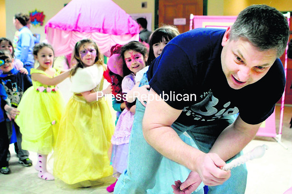 Rick Randall, playing an ice troll in a game of freeze tag, leads a conga line of kids at the recent Capes & Castles Ball held at the Imaginarium Children's Museum in Plattsburgh. Kids came dressed as their favorite princess or superhero. Fantasy-themed activities for the event were provided by the party planning company Big Blue Trunk, operated by Randall and his brother, Mike.<br><br>(BEN ROWE/P-R PHOTO)