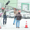 Cleaning up after a car slid off Cornelia Street on Wednesday afternoon, Plattsburgh Municipal Lighting Department workers remove the light pole it struck. <br><br>(ROB FOUNTAIN/STAFF PHOTO)