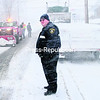 Moriah Police Officer Arthur Brassard (right) directs traffic around a flatbed tractor-trailer stuck on the Main Street hill in Port Henry on Wednesday afternoon. The truck was eventually freed with help from Ed Roberts of the Moriah Highway Department and state and village plow crews.<br><br>(LOHR McKINSTRY/STAFF PHOTO)