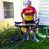 Wearing his 2013 Pan-Mass Challenge jersey, Normand Thibodeau poses with his bicycle outside of his home in Malone. This weekend, he will compete in the challenge, which raises money for cancer research, for the 15th time.<br><br>(JOHN GREEN/P-R PHOTO)