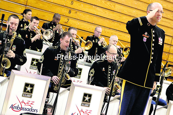 Chief Warrant Officer William S. McCulloch salutes current and veteran members of the U.S. Army and their families during a military tribute by the U.S. Army Jazz Ambassadors band. McCulloch serves as conductor for the band, which performed a mix of classic and contemporary jazz music during its performance in the SUNY Plattsburgh Field House Sunday afternoon. Toward the end of the event, the band played a medley of military anthems while recognizing military families in the audience. In particular, McCulloch thanked the members of the North Country Honor Flight in attendance at the event for their service during World War II.<br><br>(BEN ROWE/P-R PHOTO)