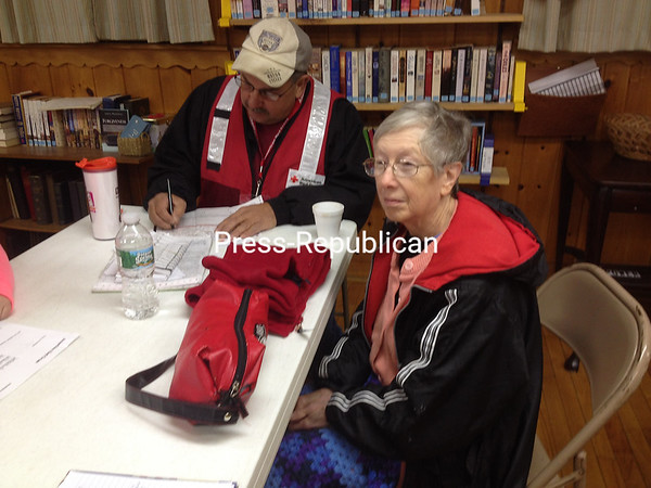 Deborah St. Clair, who alerted fellow tenants at 2423 Route 11 in Mooers to the fire there on Monday morning, regroups at the United Methodist Church in Mooers. On the table in front of her is the red vest she covered her face with as she made her way through heavy smoke from the third floor, hammering on doors as she went. To St. Clair's left is American Red Cross worker Gary Amell, preparing to fill out paperwork for her; the North Country chapter assisted 11 tenants of the building known as the old hotel, providing them with temporary lodging, financial resources and other help.