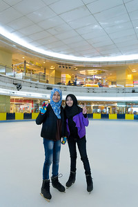 Two muslim attractive girls learn to ice skating