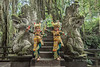 Two traditional Balinese dancers and two macaques at the Dragon Bridge, Monkey Forest Temple, Ubud, Bali