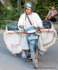 A man on a motorbike on the Monkey Forest Road in Ubud, Bali, Indonesia in June 2011. He is carrying a huge load.