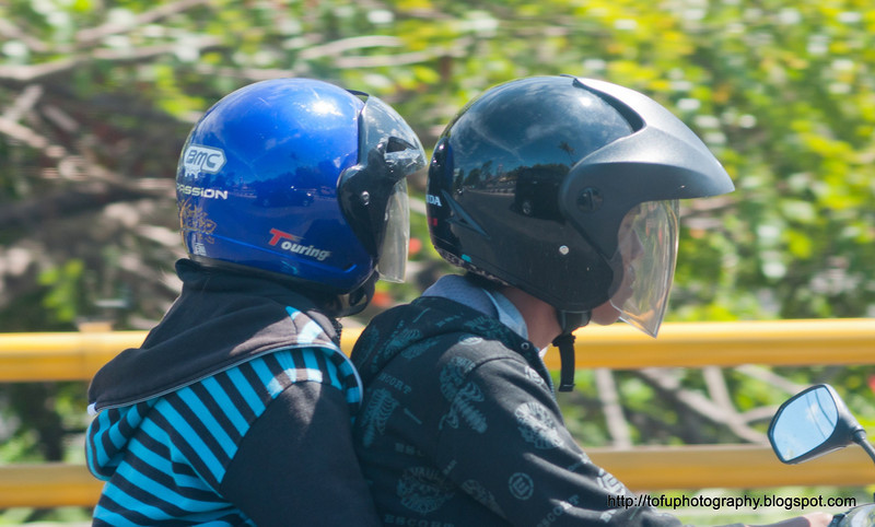 Two people riding on a motorbike with helmets somewhere between Denpasar and Ubud in Bali, Indonesia in June 2011