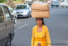 Balinese woman carrying a heavy load on her head on Jalan Suweat road in Ubud, Bali, Indonesia in June 2011