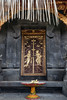 Gilded bas relief door on a pavilion (bale) and offerings, Pura Penataran Agung, Pura Besakih temple complex, Bali, Indonesia