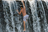 Youth climbing up the water cascade over the Tukad Unda Dam, Semarapura, Bali Island, Indonesia