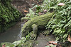 Moss-covered stone Komodo dragon 'drinking' from a stream, Sacred Monkey Forest Sanctuary, Ubud, Bali