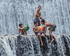Boys playing in the Tukad Unda Dam waterfall, Klongklong, Bali
