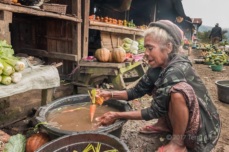 Woman washing carrots at a roadside market, East Nusa Tenggara, near Detsusoko, Indonesia