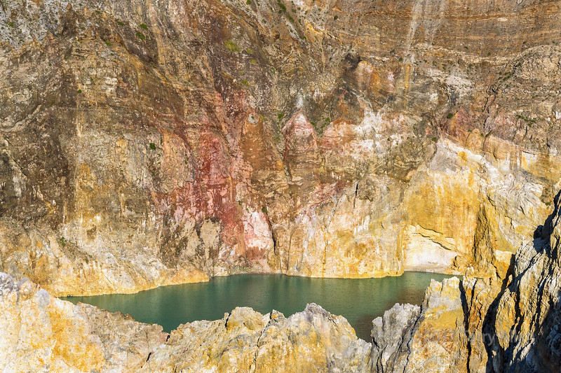 Colourful volcanic rocks with Tiwu Ata Polo crater lake (Enchanted Lake), Kelimutu National Park, East Nusa Tenggara Island, Indonesia